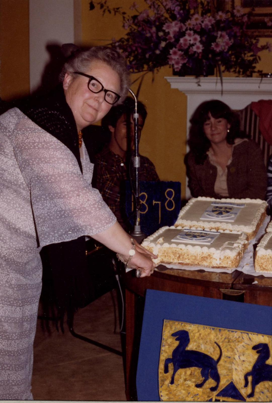 Anne Whiteman opens the LMH centenary cake1978