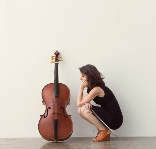 Elinor Frey with short brown hair in a black dress and brown shoes crouching by cello