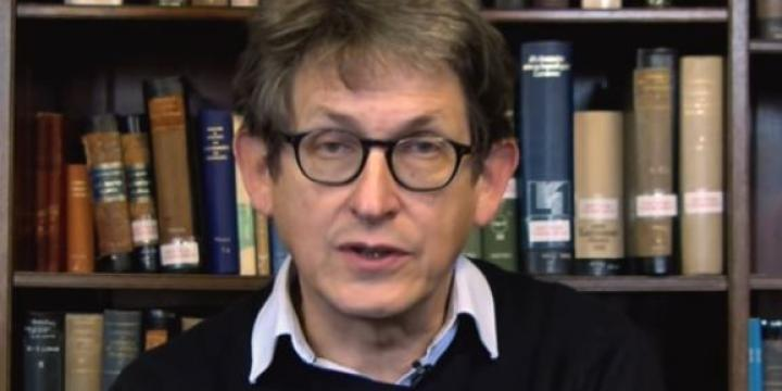 Alan Rusbridger in front of bookshelf